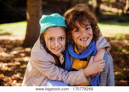 Portrait of happy siblings embracing in park during autumn