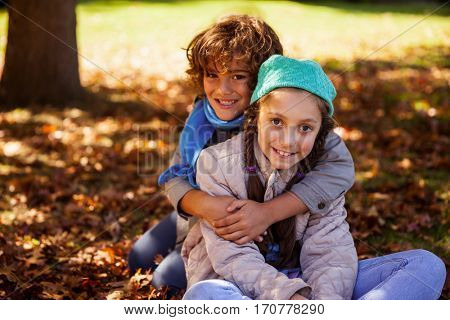 Portrait of smiling siblings embracing in park during autumn