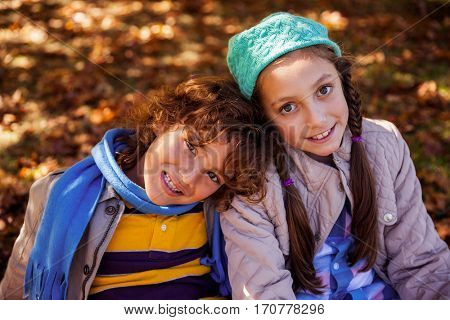 Portrait of smiling siblings sitting in park during winter