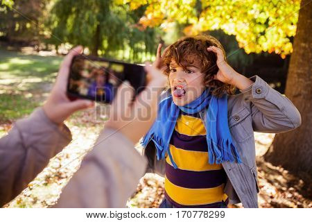 Cropped image of girl photographing boy making face in park during autumn