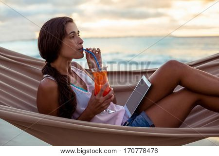 Woman having mocktail while relaxing on a hammock on the beach