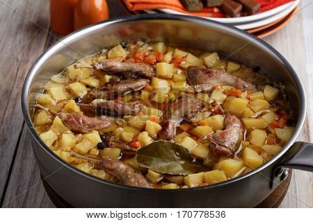 Quail legs and vegetables stew in a cooking pan