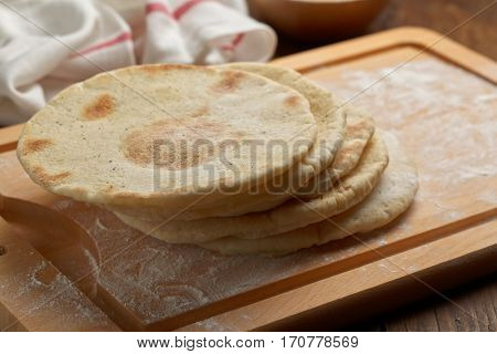 Pita breads on a chopping board