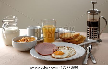 American breakfast with fried egg, ham, toasts, juice, cereal, milk, jam, and coffee