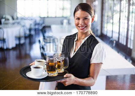 Portrait of waitress holding serving tray with coffee cup and pint of beer in restaurant