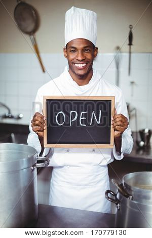 Smiling chef showing chalkboard with open sign in kitchen