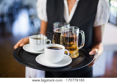 Mid section of waitress holding serving tray with coffee cup and pint of beer in restaurant