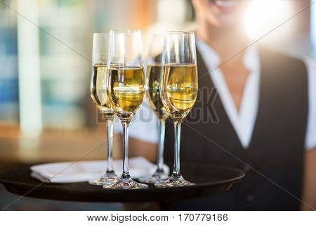 Mid section of waitress holding a serving tray with champagne flutes in restaurant