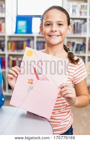 Portrait of happy schoolgirl showing her drawing in library at school