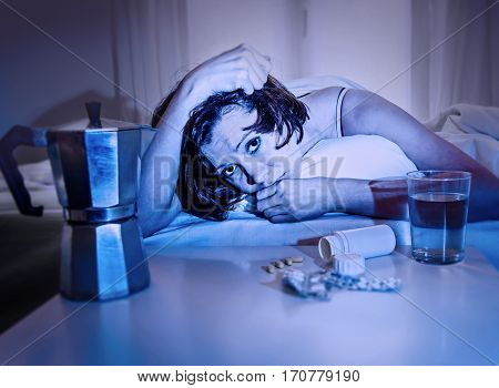 young wasted and depressed woman in bed suffering hangover after party night having water coffee and tablets looking destroyed