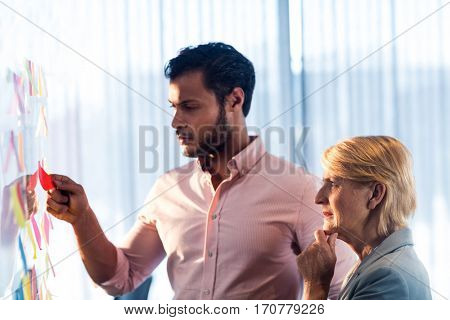 Side view of two business people looking at post it wall in office