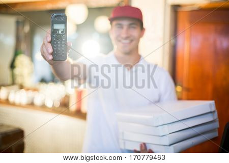 Pizza delivery man in restaurant holding phone