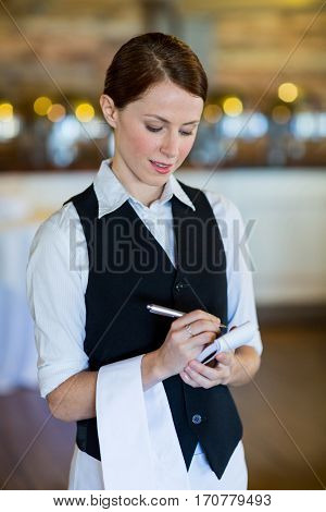 Smiling waitress taking order in restaurant