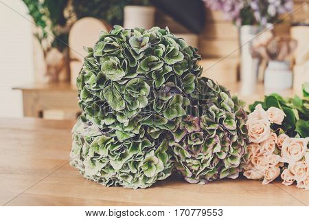 Floristic shop background. Green flowers and fresh roses for bouquet delivery. Floral design studio, making decorations and arrangements.