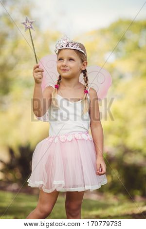 Young girl pretending to be a fairy in park