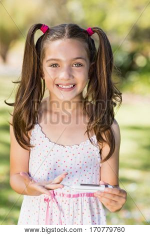 Portrait of cute girl testing diabetes on glucose meter in park