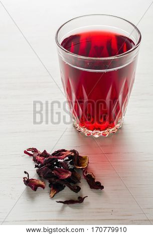 Hibiscus Tea In A Glass Mug On A Wooden Table Among Rose Petals And Dry Tea Custard