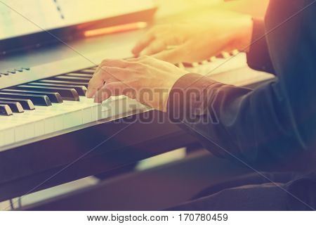 pianist hands playing piano in a outdoor concert with sun flare and warm light