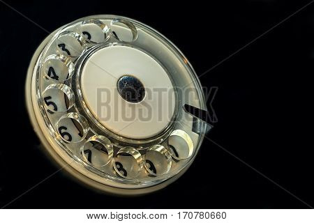 antique retro telephone circle with numbers on the black background angle view with copy space