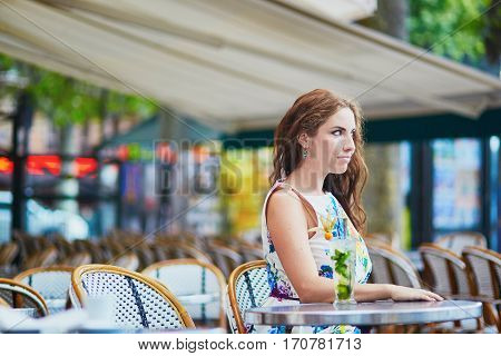 Woman In Parisian Cafe With Cocktail On A Summer Day