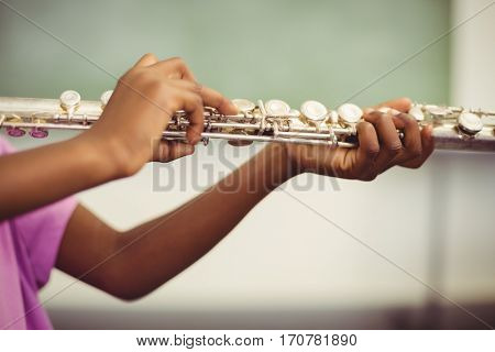 Schoolgirl playing flute in classroom at school