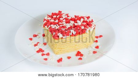 Pile of pancakes in the shape of a heart on white plate with many little sugar hearts