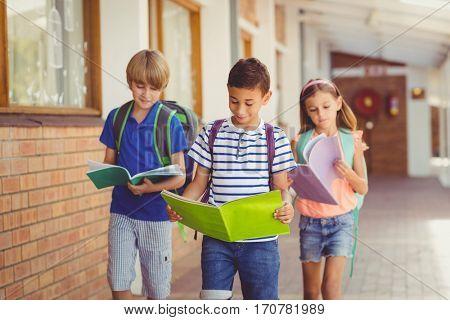 School kids reading books while walking in corridor at school