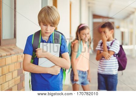School friends bullying a sad boy in corridor at school