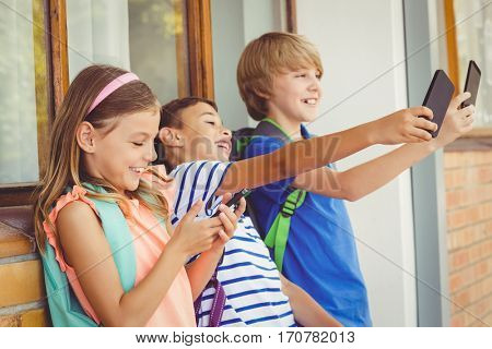 School kids taking selfie and using mobile phone in corridor at school