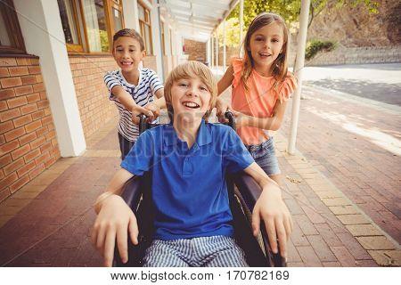 Portrait of school kids pushing a boy on wheelchair in school corridor