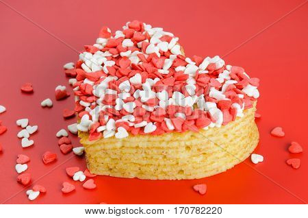 Pile of pancakes in the shape of a heart on red background with little sugar hearts