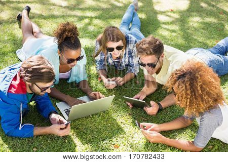 Group of friends using laptop, mobile phone and digital tablet in park