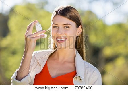 Portrait of beautiful woman using asthma inhaler in park