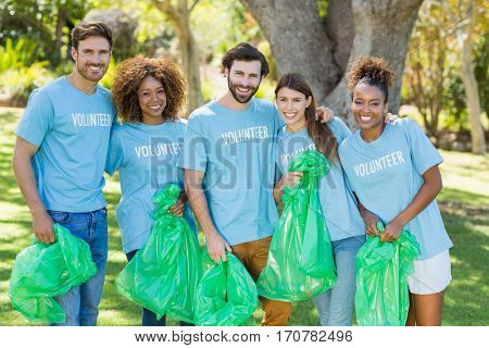 Portrait of volunteer group posing while collecting rubbish in park