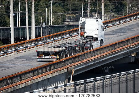 one white truck on road rides up over the bridge, industrial infrastructure, cargo transportation, delivery and shipping concept