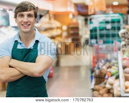 Portrait of man grocer smiling with his arms crossed