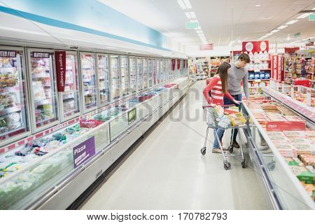 Serious couple doing grocery shopping together at grocery store