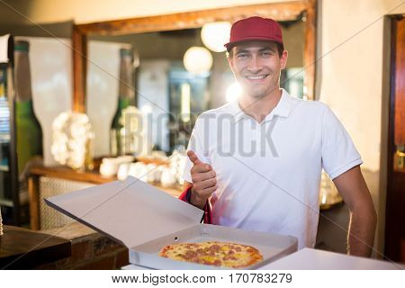 Pizza delivery man showing fresh pizza and thumbs up in restaurant