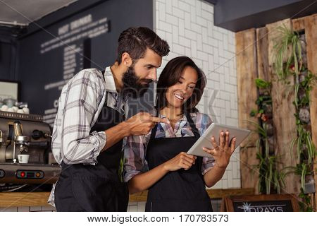 Two waiters using a tablet computer in the bar