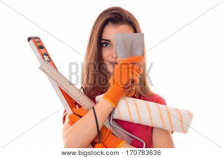 cutie young brunette lady makes renovation in gloves with tools in her hands isolated on white
