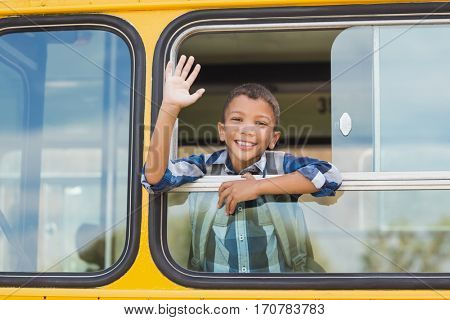 Portrait of smiling schoolboy waving hand from bus