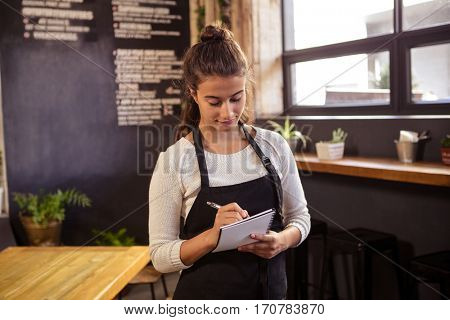 Beautiful waitress taking order in cafeteria