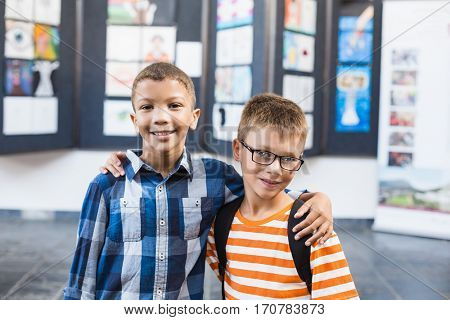 Portrait of smiling school kids standing with arm around in classroom at school