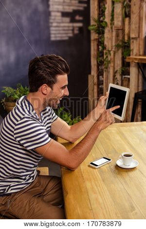 Young man sitting at table using digital tablet in cafeteria