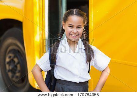 Portrait of smiling schoolgirl standing with hand on hip in front of school bus