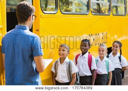 Teacher updating check list of kids while entering in bus