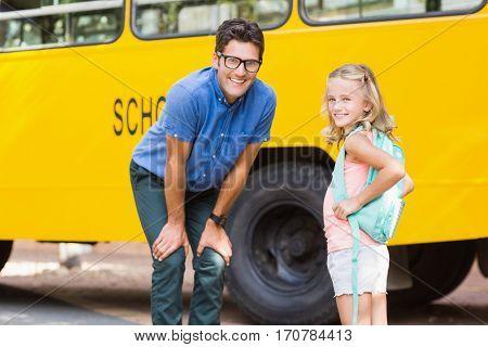 Portrait of smiling teacher and schoolgirl standing in front of school bus
