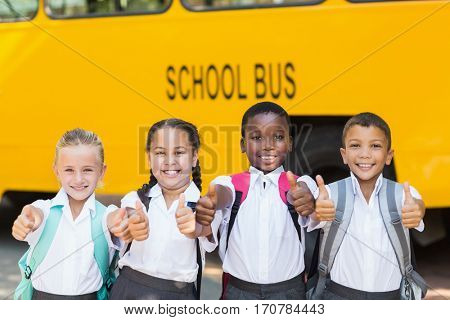 Portrait of smiling kids showing thumbs up in front of school bus