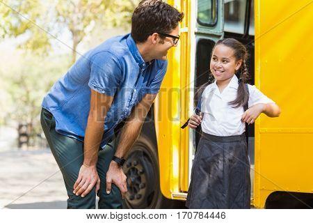 Smiling teacher and schoolgirl interacting in front of school bus
