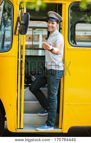 Smiling bus driver standing at the entrance of bus and gesturing